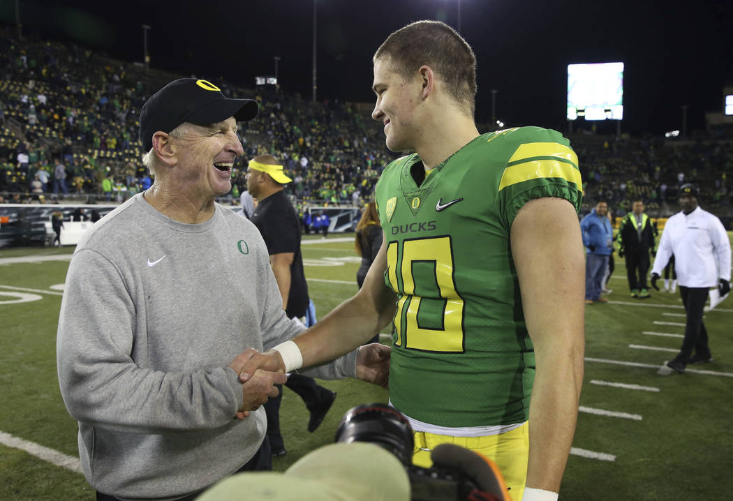 Oregon defensive coordinator Jim Leavitt, left, congratulates quarterback Justin Herbert after an NCAA college football game against Arizona, Saturday, Nov. 18, 2017, in Eugene, Ore. Oregon defeat ...