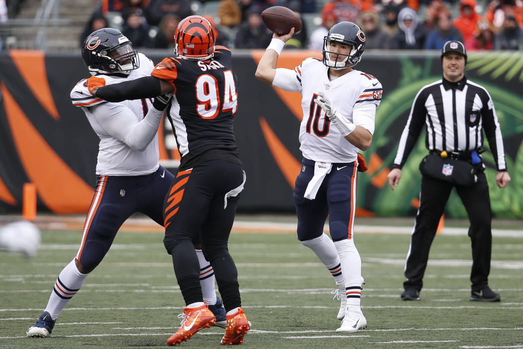 Chicago Bears quarterback Mitchell Trubisky (10) passes under pressure from Cincinnati Bengals defensive end Chris Smith (94) in the first half of an NFL football game, Sunday, Dec. 10, 2017, in C ...
