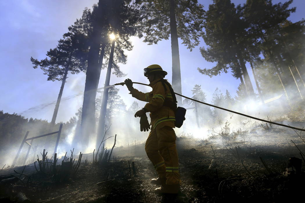 Monte Rio volunteer firefighter Gabriela Gibson sprays down hot spots on a half-acre fire in timber above Monte Rio, Calif., after a controlled burn crossed containment lines and wind blew embers  ...