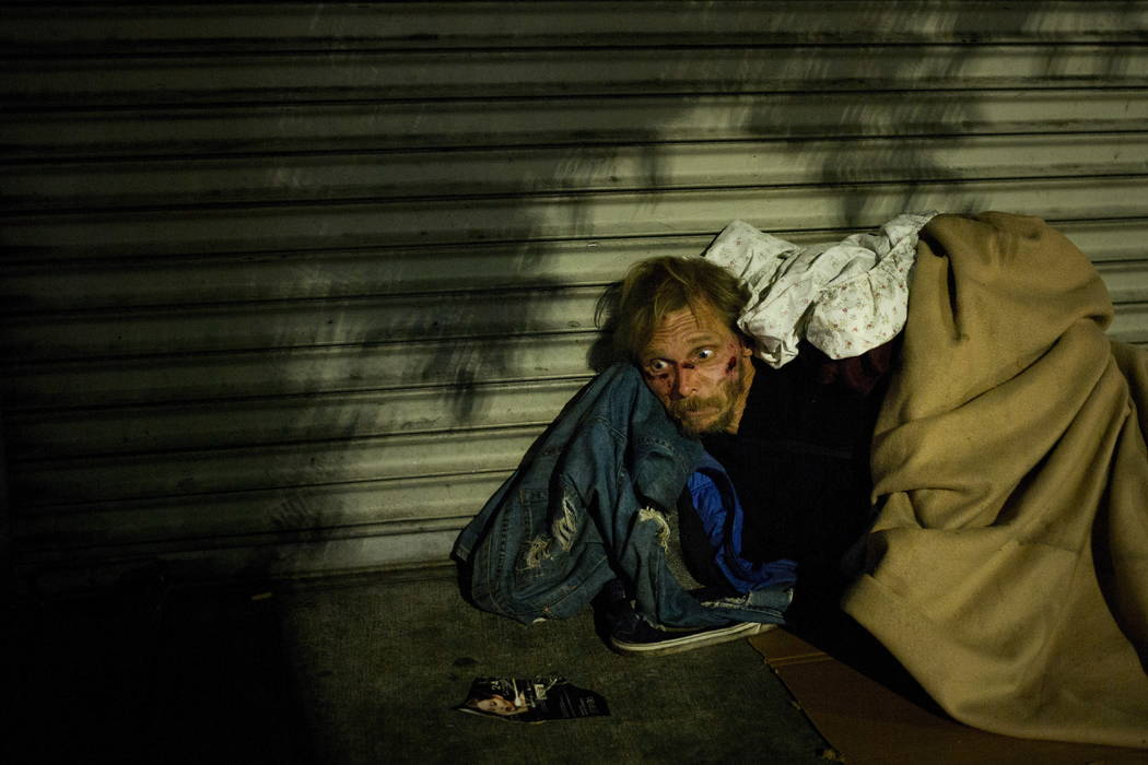 Bearing cuts all over his face, a homeless drug addict, who said his name is April Jane, aimlessly stares into space on a sidewalk in the Skid Row area of downtown Los Angeles, Thursday, Nov. 2, 2 ...