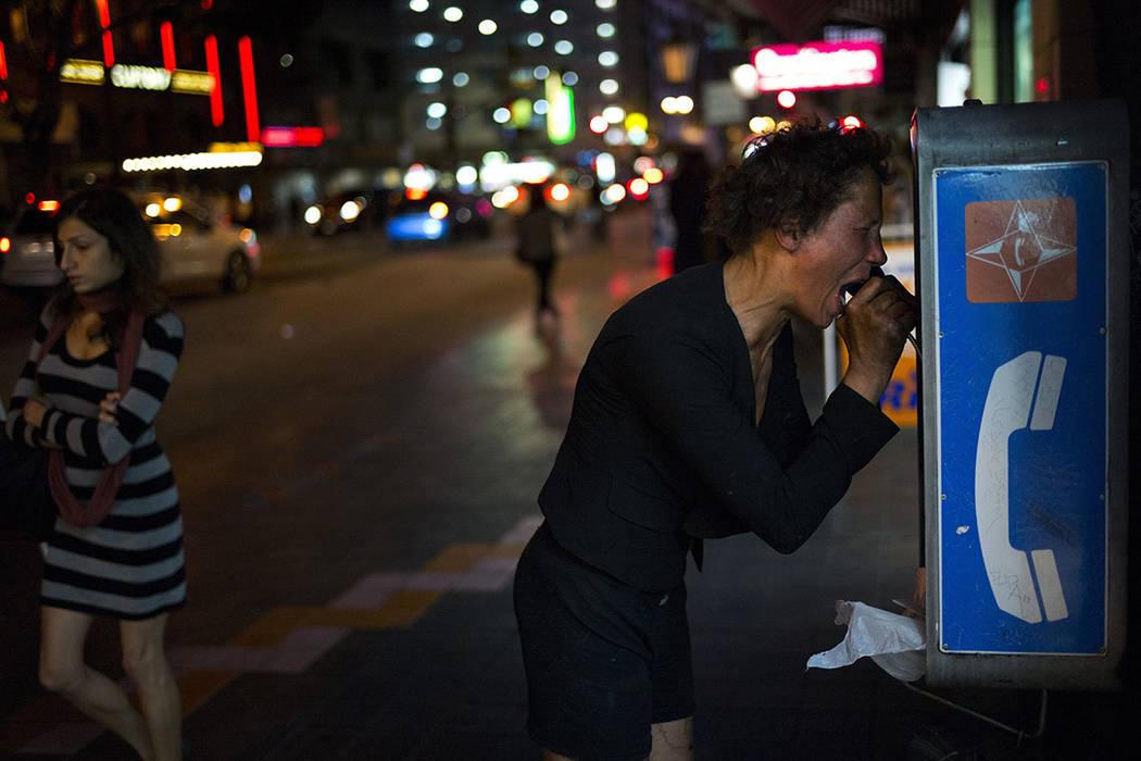 A mentally ill homeless woman cries out while holding a pay phone after running through several blocks of downtown Los Angeles, yelling and screaming Saturday, Nov. 4, 2017. (AP Photo/Jae C. Hong)