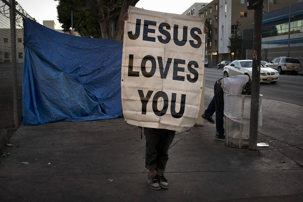 "Samuel Raymond, 50, holds up a banner saying ""Jesus Loves You"" on a sidewalk as a passing homeless man reaches into a trash can in search of anything of value Saturday, Nov. 4, 2017, in the Skid R ..."