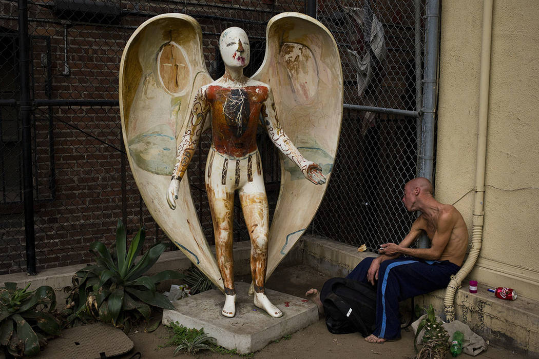 Homeless drug addict Andrew Hudson, 33, reacts as he injects himself with heroin next to an angel statue Wednesday, Nov. 8, 2017, in the Skid Row area of downtown Los Angeles. (AP Photo/Jae C. Hong)