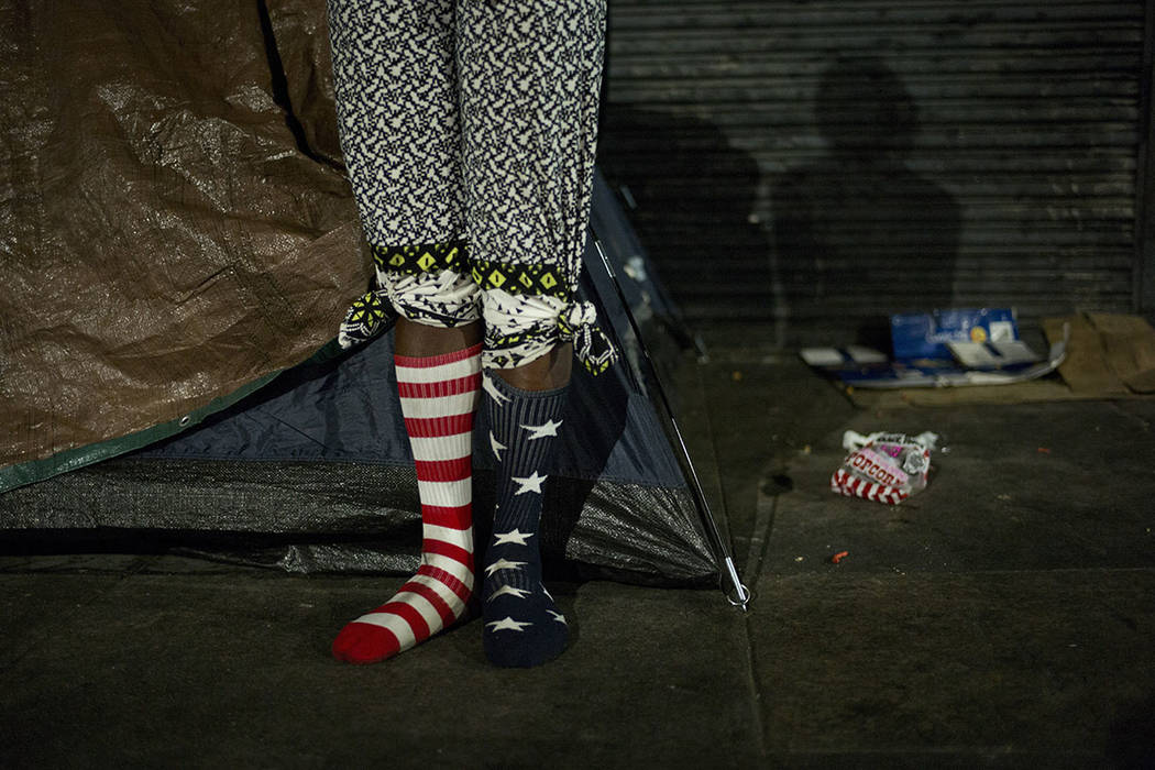 Wearing a pair of American flag socks, homeless Stafford Wilson, 48, stands in front of his tent while dancing to music Tuesday, Nov. 7, 2017, in the Skid Row area of downtown Los Angeles. (AP Pho ...
