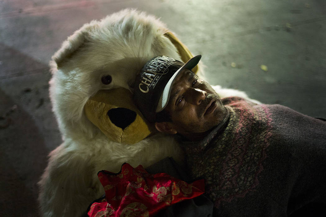 Using a teddy bear named Michelle as a pillow, Manuel Martinez, a 45-year-old homeless day laborer originally from Mexico, falls asleep on a sidewalk in the Skid Row area of downtown Los Angeles,  ...