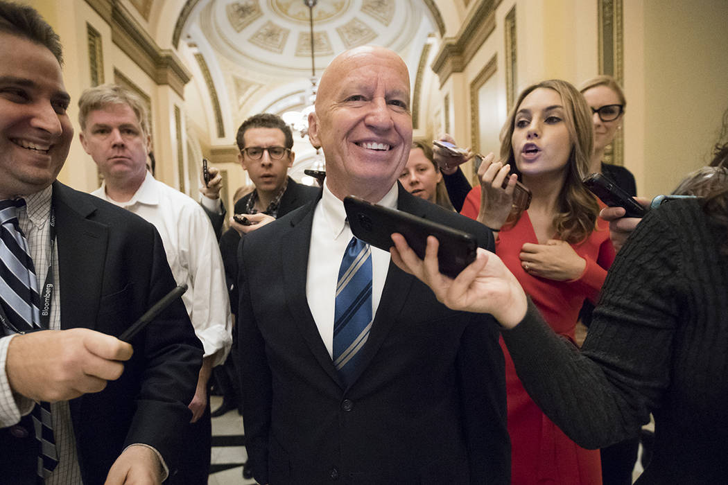 House Ways and Means Committee Chairman Kevin Brady, R-Texas, is pursued by reporters in the Capitol after signing the conference committee report to advance the GOP tax bill, in Washington, Frida ...