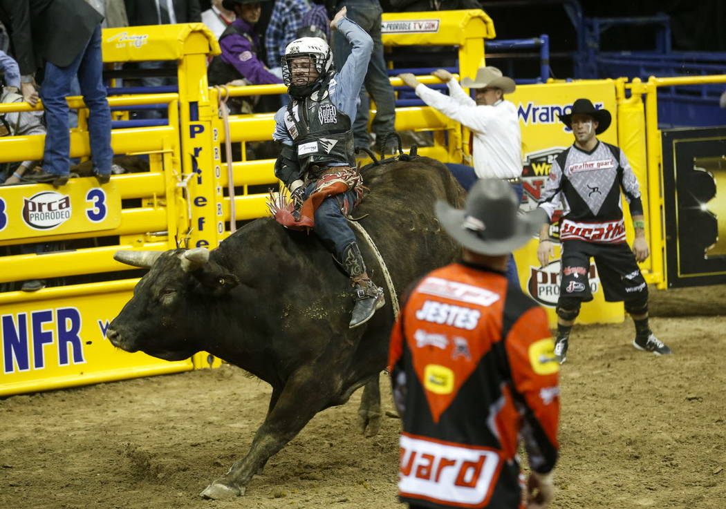 Trey Benton III of Rock Island, Texas rides Nose Bender in the bull riding competition during the ninth go-round of the National Finals Rodeo, Friday, Dec. 15, 2017, at the Thomas & Mack Cente ...