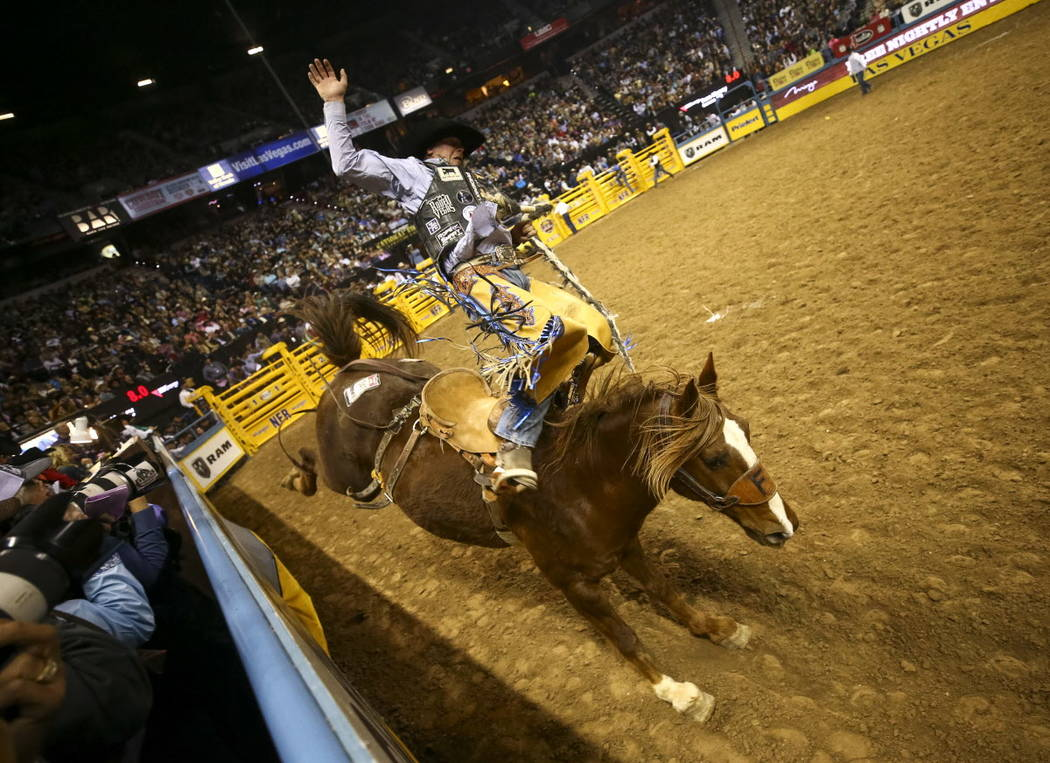 Taos Muncy of Corona, New Mexico rides Tip Off in the saddle bronc riding competition during the ninth go-round of the National Finals Rodeo, Friday, Dec. 15, 2017, at the Thomas & Mack Center ...