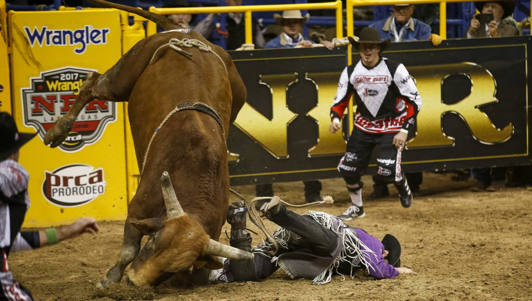 Tim Bingham, of Honeyville, Utah hits the dirt after getting bucked from Hot and Ready in the bull riding competition during the ninth go-round of the National Finals Rodeo, Friday, Dec. 15, 2017, ...