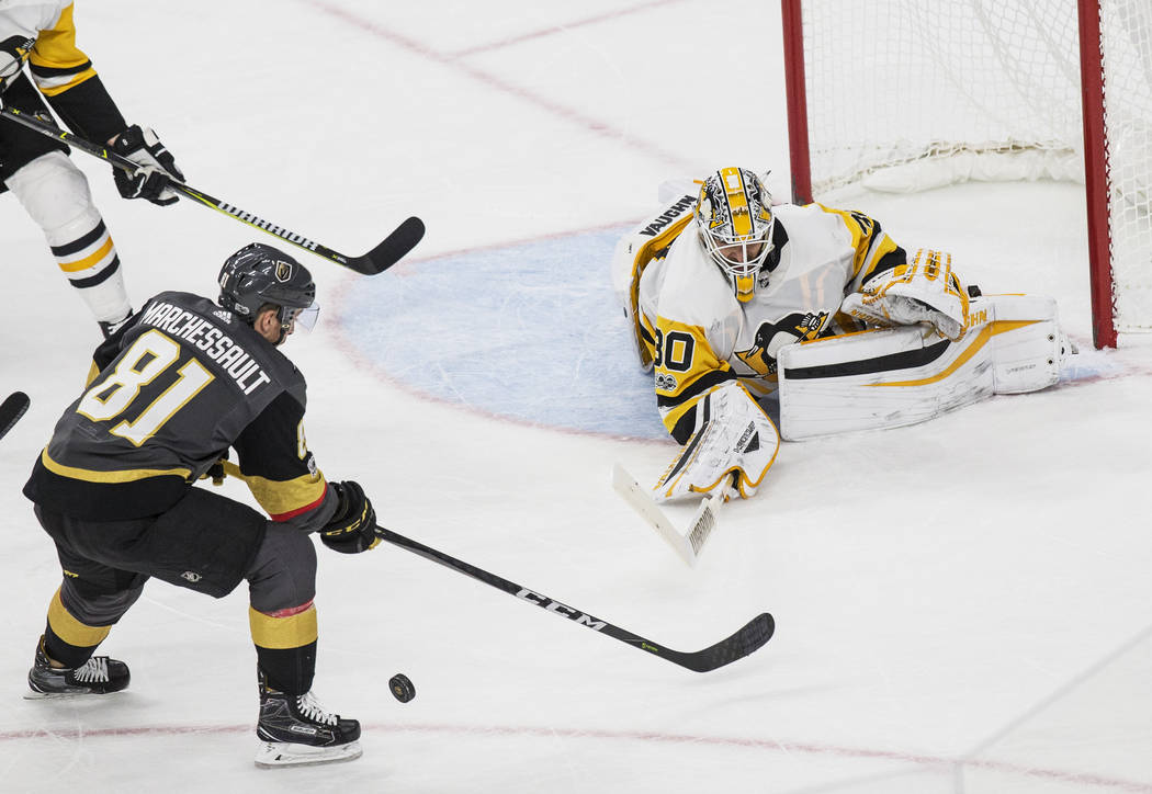 Pittsburgh goaltender Matt Murray (30) punches a shot away from Golden Knights center Jonathan Marchessault (81) in the third period during Vegas' home matchup with the Penguins on Thursday, Dec.  ...
