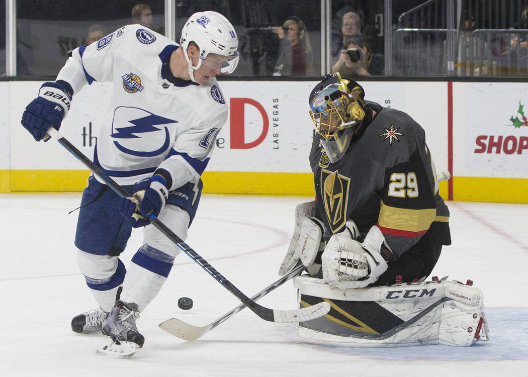 Golden Knights goaltender Marc-Andre Fleury (29) makes a save against Tampa Bay left wing Ondrej Palat (18) in the first period during Vegas' home matchup with the Lighting on Tuesday, Dec. 19, 20 ...