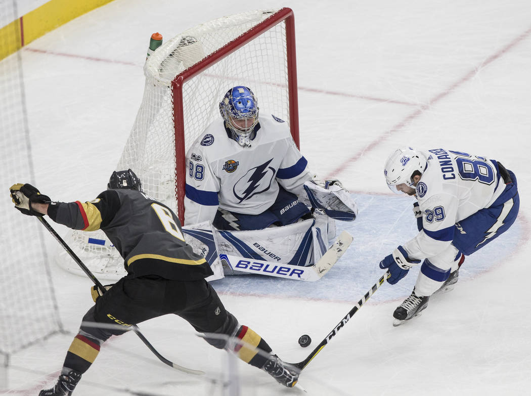 Golden Knights defenseman Colin Miller (6) fights for a puck with Tampa Bay center Cory Conacher (89) and goaltender Andrei Vasilevskiy (88) in the third period  during Vegas' home matchup with th ...