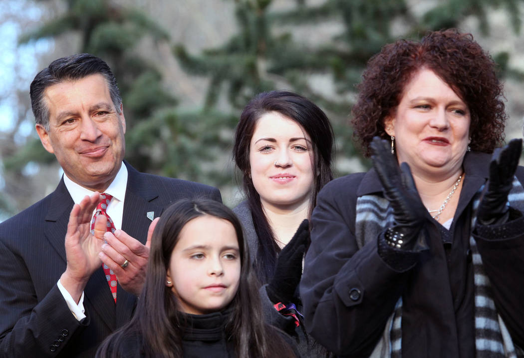 Nevada Gov. Brian Sandoval looks on with his family first lady Kathleen Sandoval and daughters Marisa, 10, and Maddy, 18, as they watch Robert McQueen High School choir from Reno Nevada performs d ...