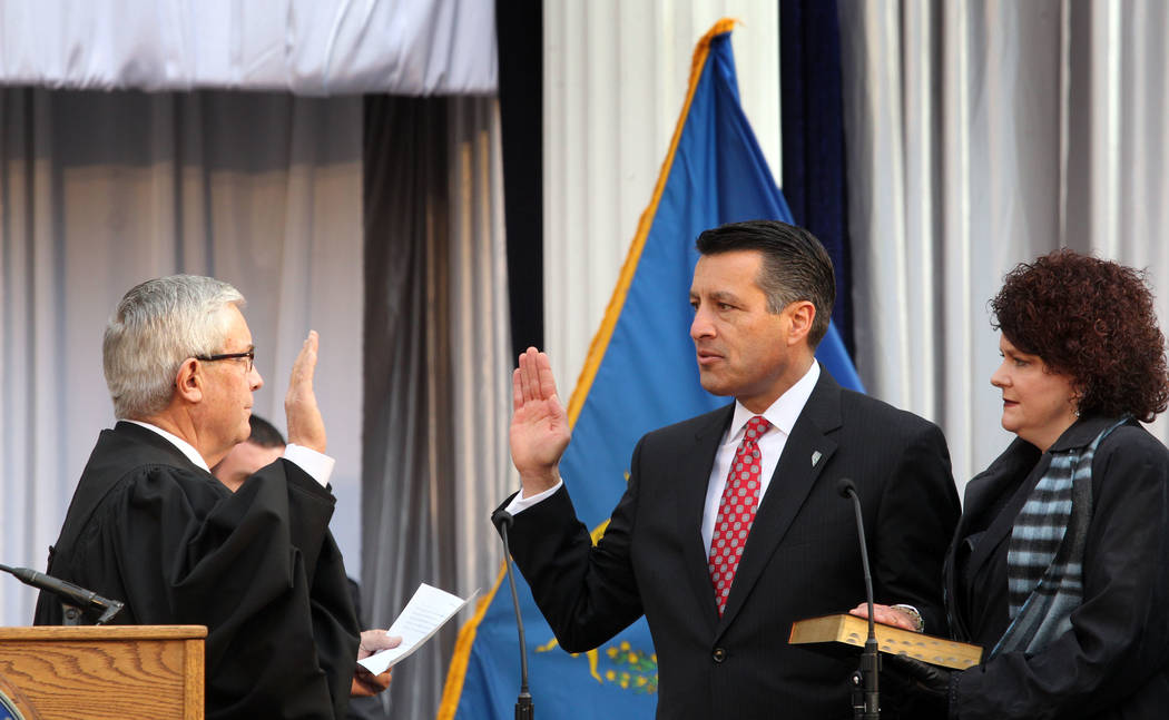 Nevada Gov. Brian Sandoval, center, holds his hand on a bible held by his wife first lady Kathleen Sandoval as he takes the oath of office during his inauguration ceremony on the front steps of th ...