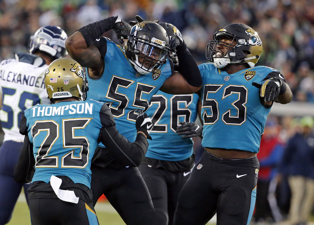 Jacksonville Jaguars players celebrate after a big play against the Seattle Seahawks during the first half of an NFL football game, Sunday, Dec. 10, 2017, in Jacksonville, Fla. (AP Photo/Stephen B ...