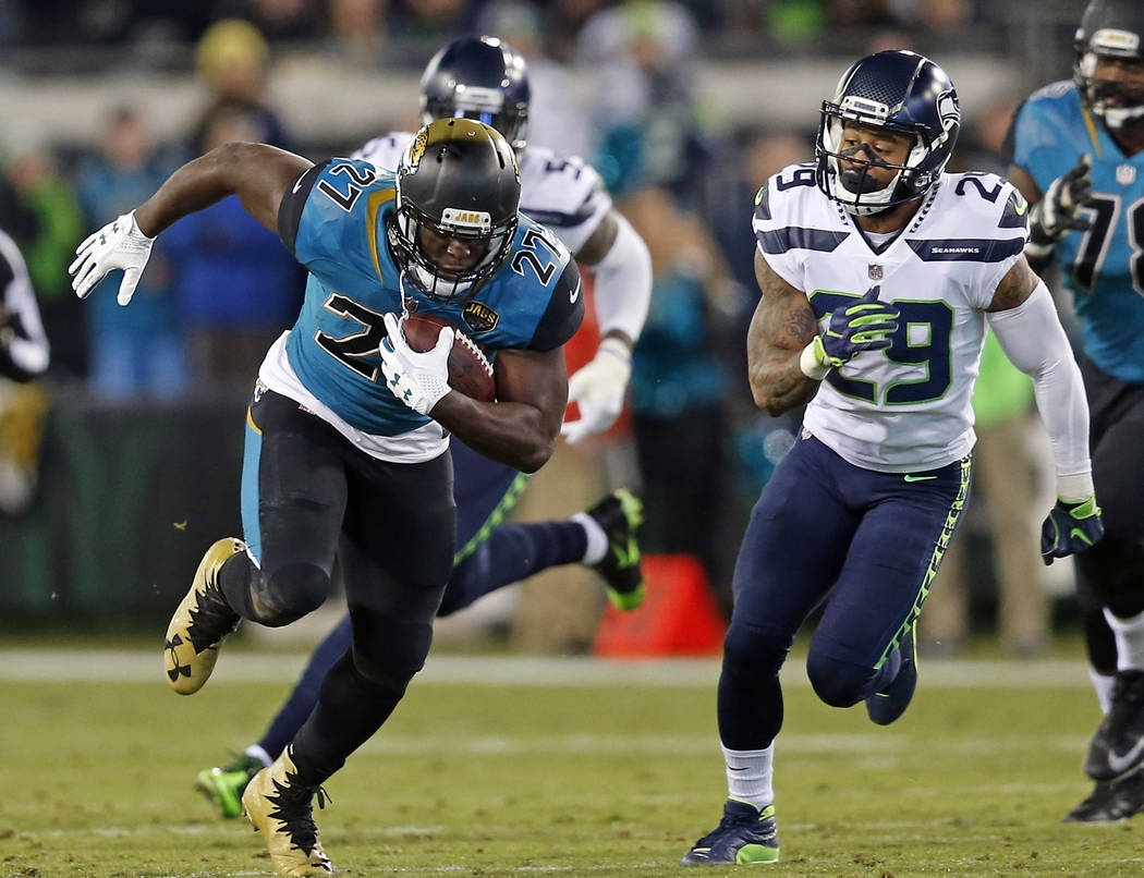 Jacksonville Jaguars running back Leonard Fournette (27) runs for yardage past Seattle Seahawks safety Earl Thomas (29) during the second half of an NFL football game, Sunday, Dec. 10, 2017, in Ja ...