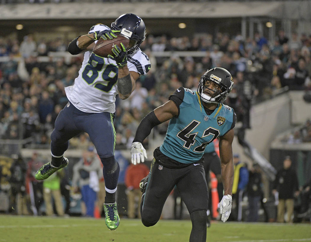 Seattle Seahawks wide receiver Doug Baldwin, left, catches a pass for a 26-yard touchdown in front of Jacksonville Jaguars safety Barry Church (42) during the second half of an NFL football game,  ...