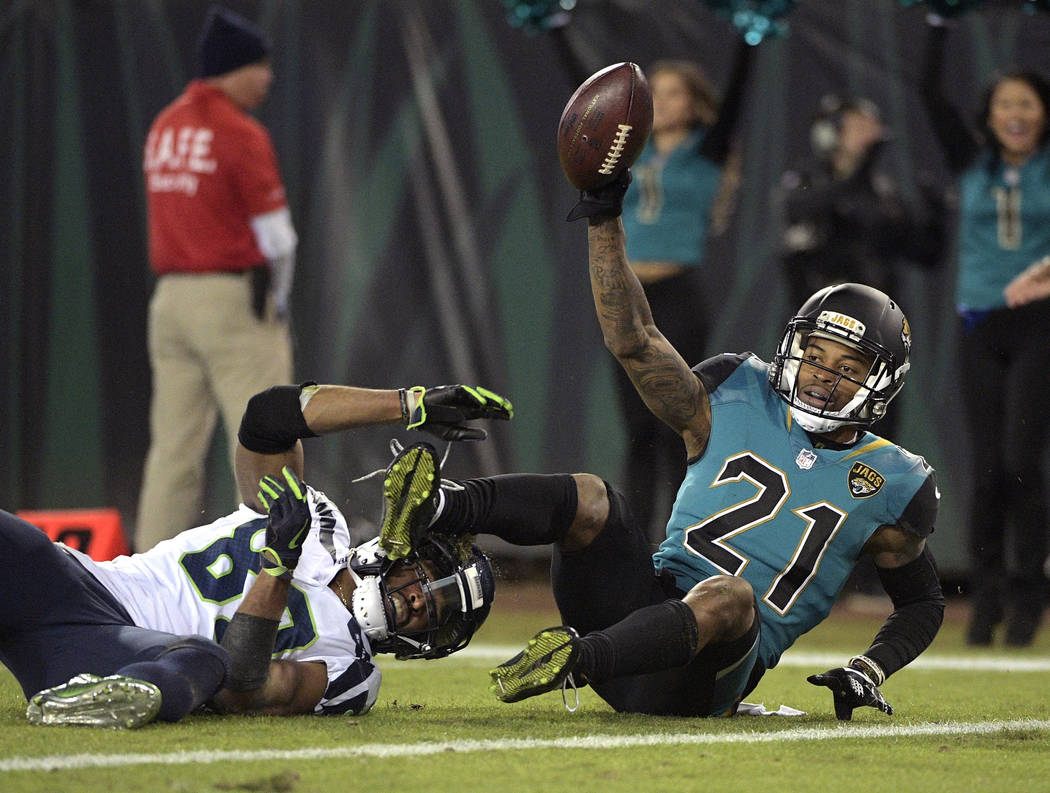 Jacksonville Jaguars cornerback A.J. Bouye (21) holds up the ball after he intercepted a pass in the end zone intended for Seattle Seahawks wide receiver Doug Baldwin, left, during the second half ...