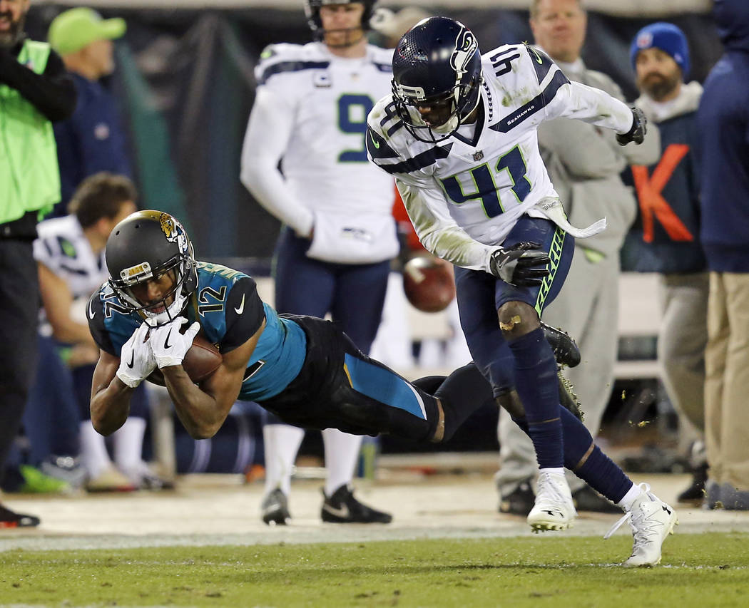FILE - In this Dec. 10, 2017, file photo, Jacksonville Jaguars wide receiver Dede Westbrook (12) catches a pass over Seattle Seahawks cornerback Byron Maxwell (41) during the second half of an NFL ...