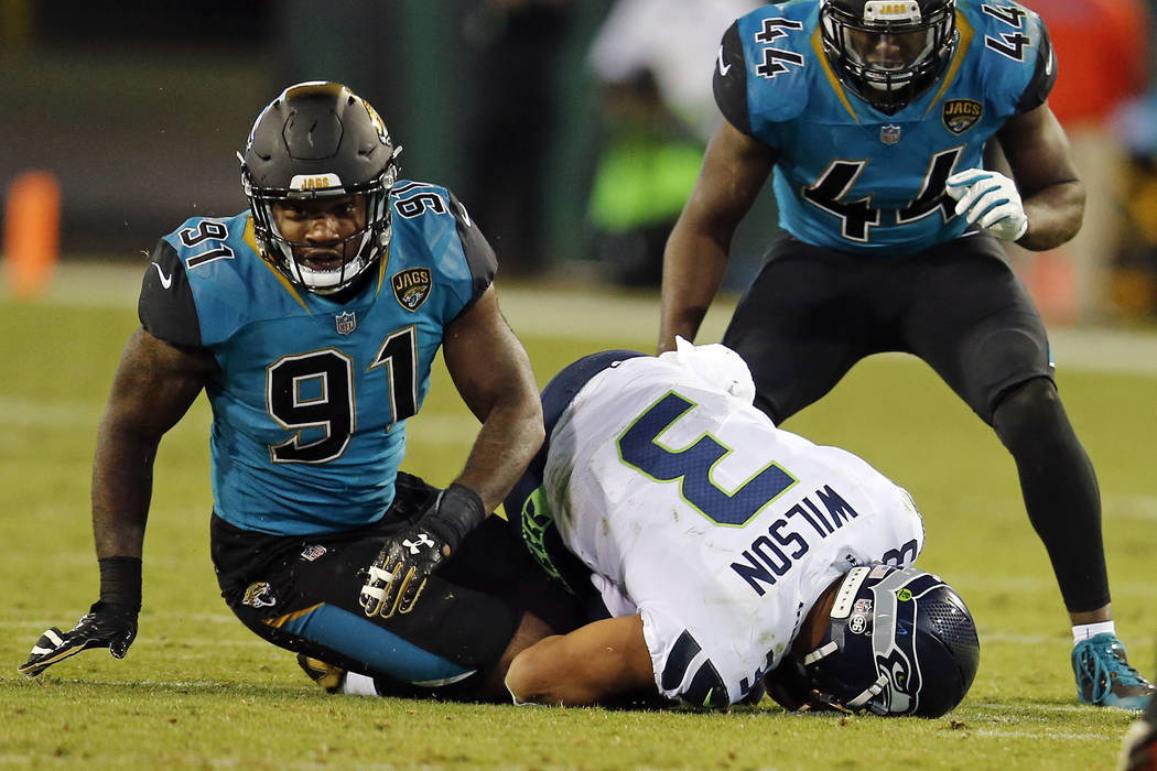 Seattle Seahawks quarterback Russell Wilson (3) is sacked by Jacksonville Jaguars defensive end Yannick Ngakoue (91) and Myles Jack (44) during the second half of an NFL football game, Sunday, Dec ...