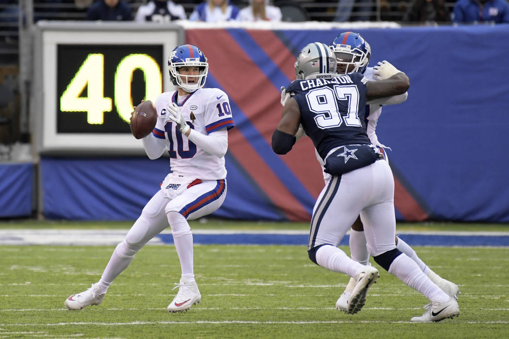 New York Giants quarterback Eli Manning (10) looks to pass as Dallas Cowboys defensive end Taco Charlton (97) closes in during the fourth quarter of an NFL football game, Sunday, Dec. 10, 2017, in ...