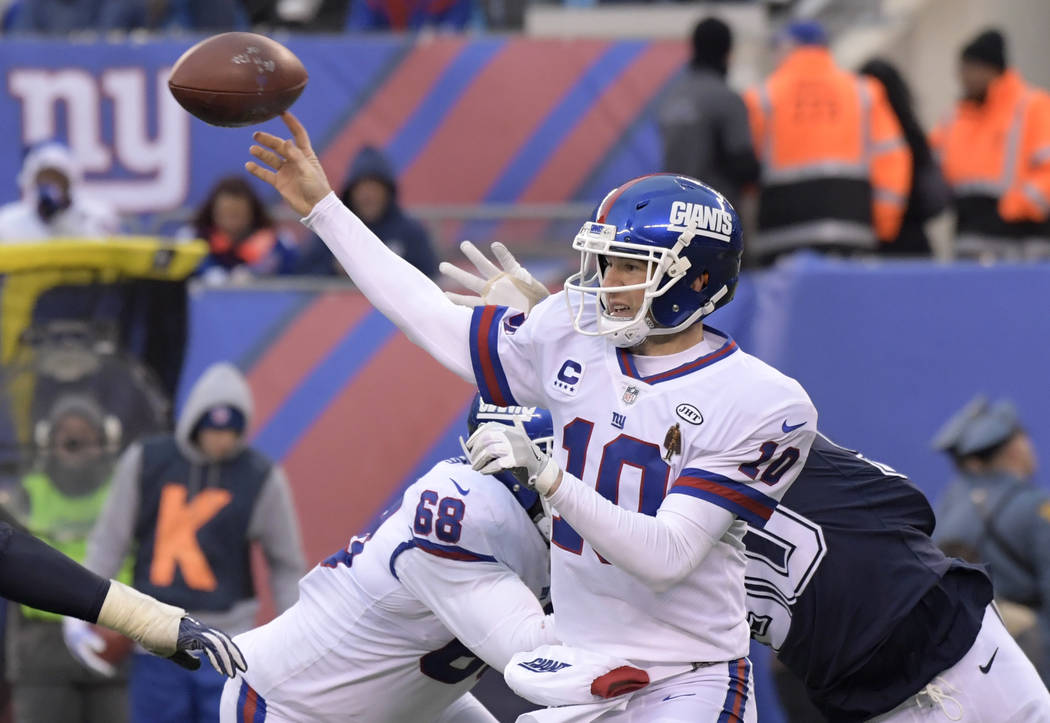 New York Giants quarterback Eli Manning (10) throws a pass during the second half of an NFL football game against the Dallas Cowboys, Sunday, Dec. 10, 2017, in East Rutherford, N.J. (AP Photo/Bill ...