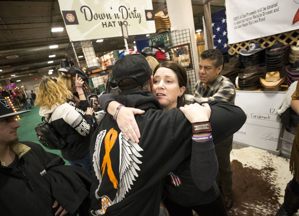 Natalie Grumet, who was shot in the face during the Route 91 Harvest festival, hugs a fellow survivor at the Down N Dirty Hat Company booth during the Stetson Country Christmas expo at the Sa ...