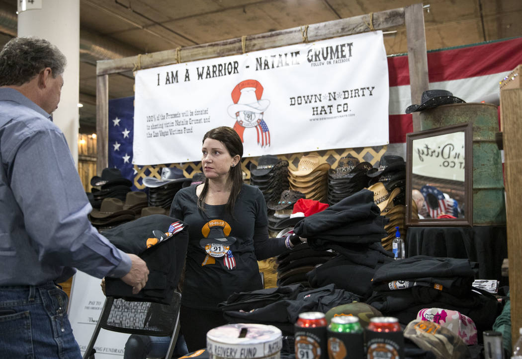 Natalie Grumet, right, who was shot in the face during the Route 91 Harvest festival, sells memorial T-shirts to help raise money for her medical bills at the Down N Dirty Hat Company booth during ...