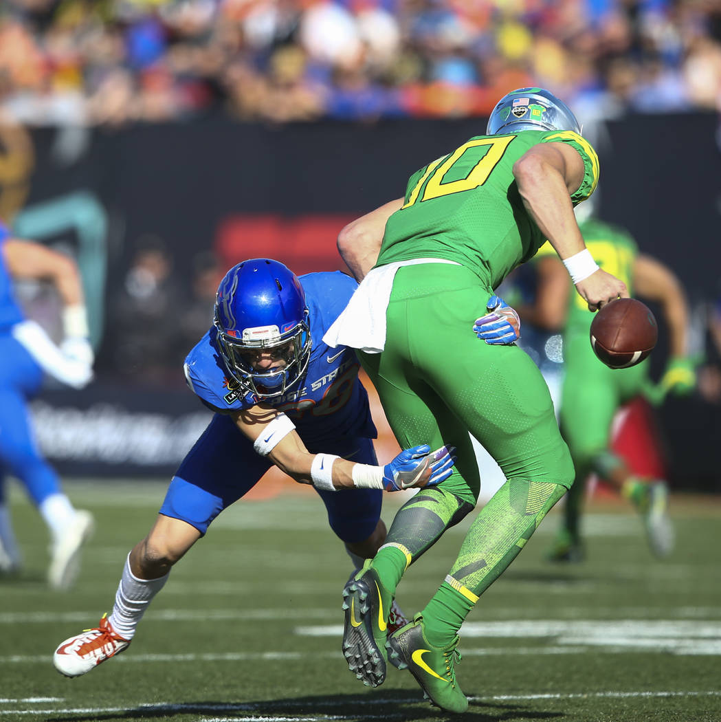 Oregon's Justin Herbert (10) gets sacked by Boise State's Kekaula Kaniho (28) during the Las Vegas Bowl at Sam Boyd Stadium in Las Vegas on Saturday, Dec. 16, 2017. Chase Stevens Las Vegas Review- ...