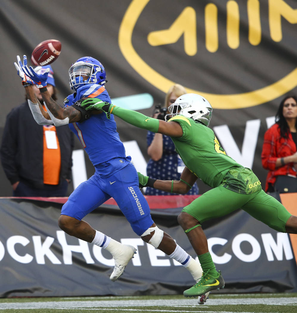 Boise State's Cedrick Wilson (1) goes up to receive a long pass as Oregon's Thomas Graham Jr. (4) attempts to tackle during the Las Vegas Bowl at Sam Boyd Stadium in Las Vegas on Saturday, Dec. 16 ...