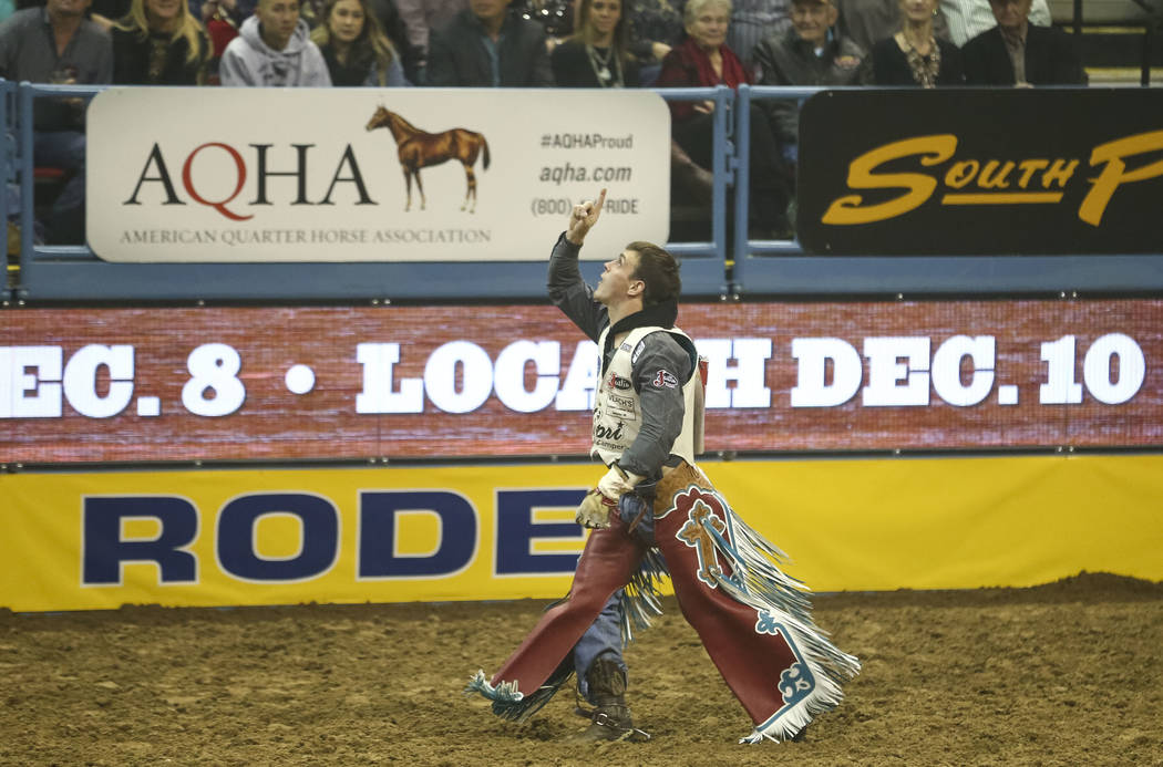 Tim O'Connell of Zwingle, Iowa points to the sky after riding Mucho Dinero in the bareback riding competition in the tenth go-round of the National Finals Rodeo, Saturday, Dec. 16, 2017, at the Th ...