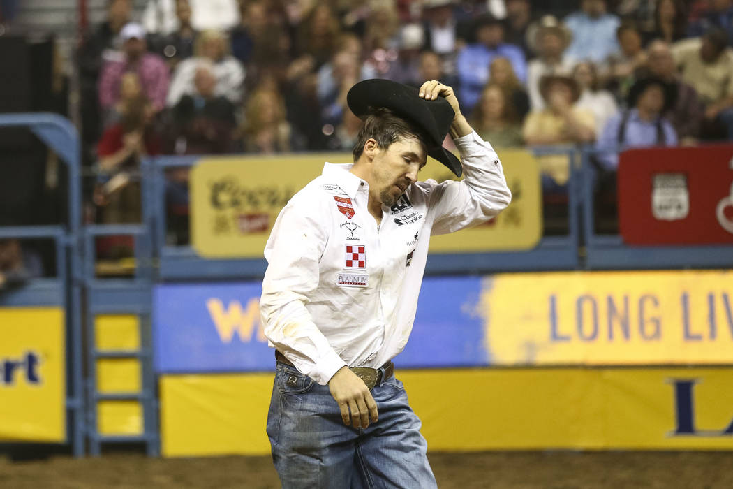 Tyler Pearson of Louisville, Mississippi tips his hat to the crowd after taking part in the steer wrestling competition in the tenth go-round of the National Finals Rodeo, Saturday, Dec. 16, 2017, ...