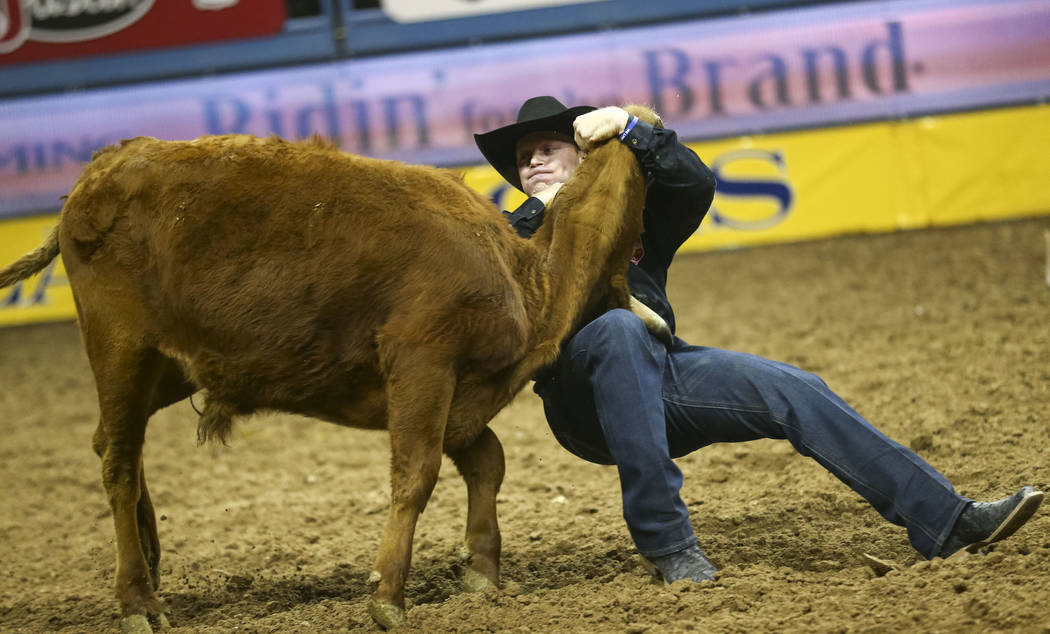 Dakota Eldridge of Elko, Nevada takes part in the steer wrestling competition in the tenth go-round of the National Finals Rodeo, Saturday, Dec. 16, 2017, at the Thomas & Mack Center in Las Ve ...