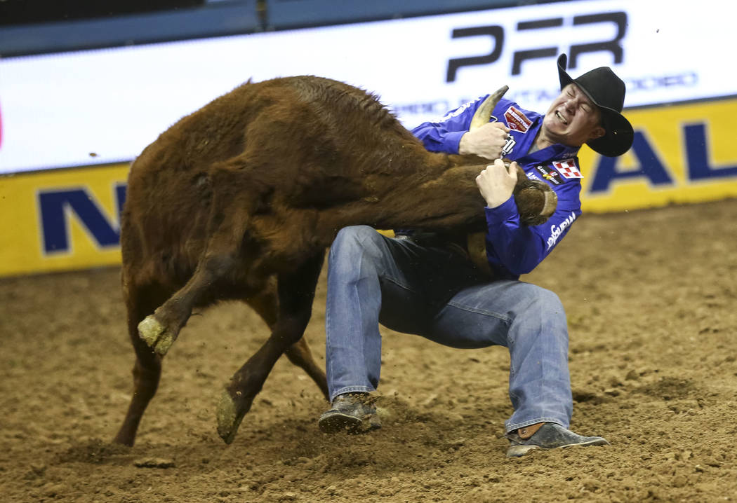 Ty Erickson of Helena, Montana takes part in the steer wrestling competition in the tenth go-round of the National Finals Rodeo, Saturday, Dec. 16, 2017, at the Thomas & Mack Center in Las Veg ...