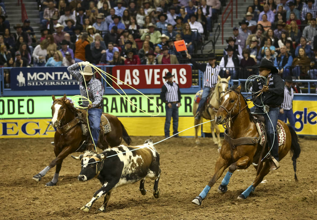 Cory Petska, left, and Erich Rogers, both from Arizona, take part in the team roping competition in the tenth go-round of the National Finals Rodeo, Saturday, Dec. 16, 2017, at the Thomas & Ma ...