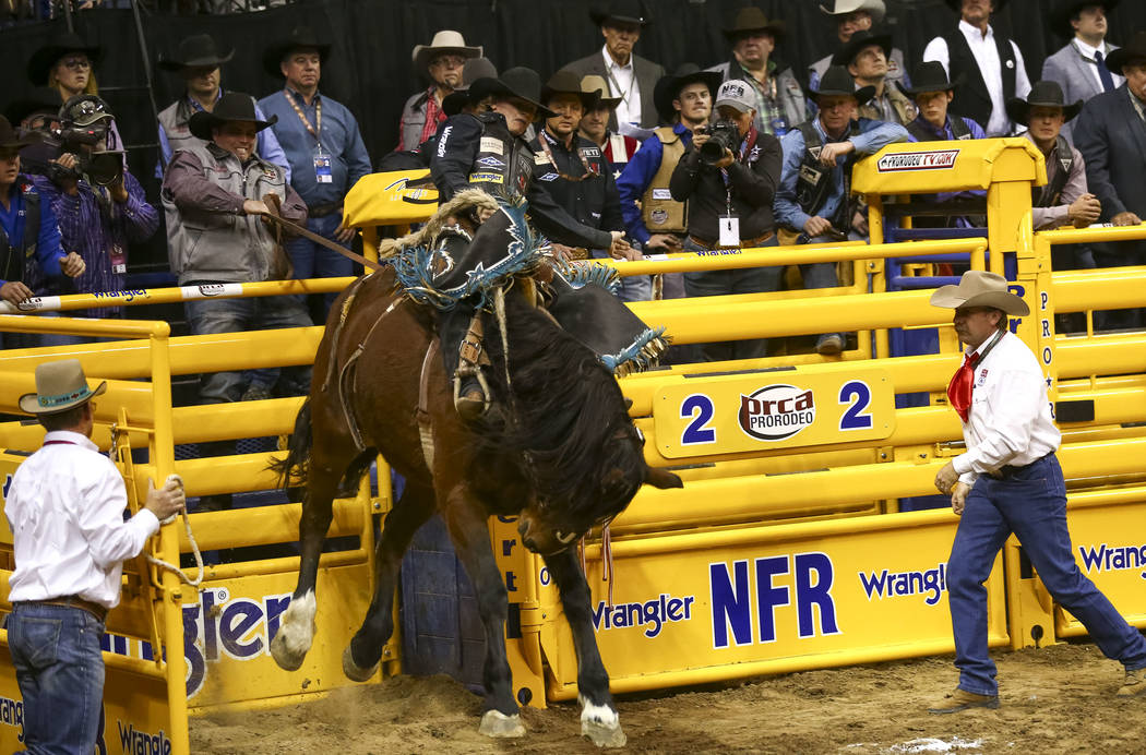 Ryder Wright of Milford, Utah comes out of the chute on Prom Night during the saddle bronc riding competition in the tenth go-round of the National Finals Rodeo, Saturday, Dec. 16, 2017, at the Th ...