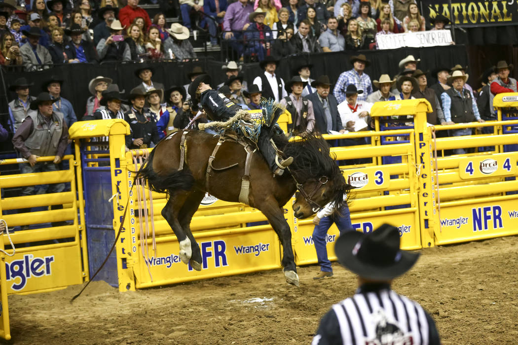 Ryder Wright of Milford, Utah rides Prom Night during the saddle bronc riding competition in the tenth go-round of the National Finals Rodeo, Saturday, Dec. 16, 2017, at the Thomas & Mack Cent ...