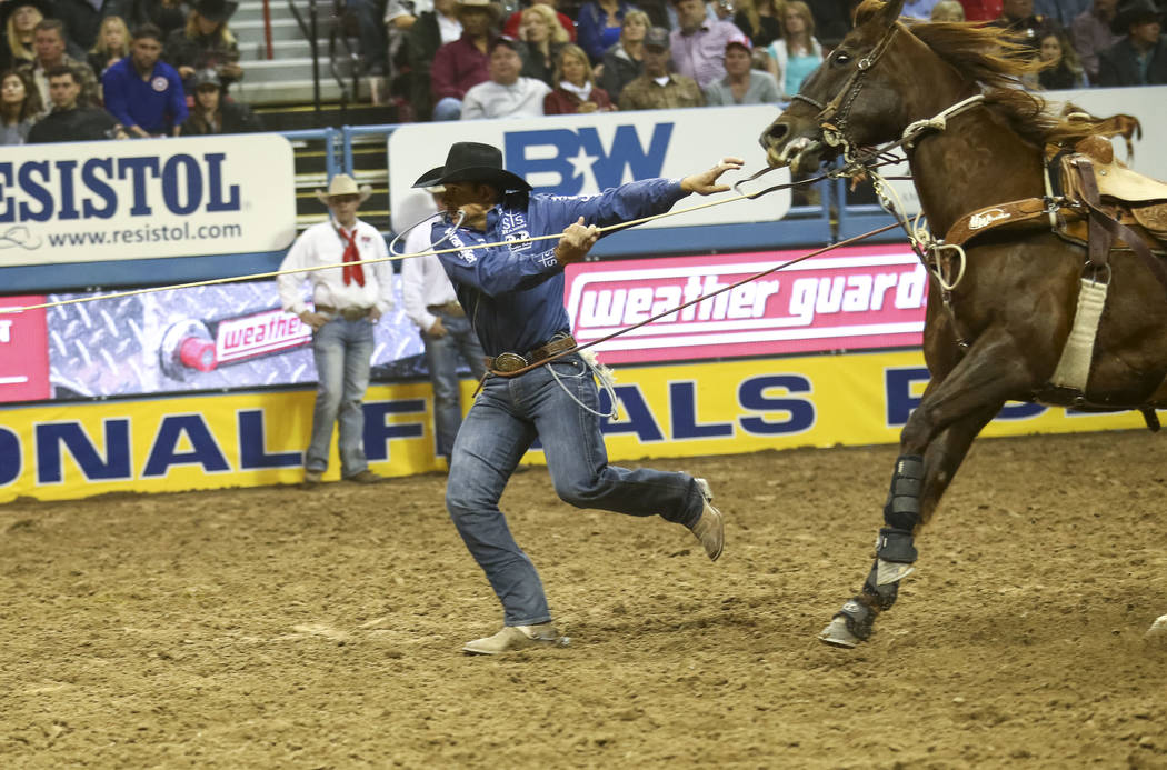 Marcos Costa of Childress, Texas takes part in the tie-down roping competition in the tenth go-round of the National Finals Rodeo, Saturday, Dec. 16, 2017, at the Thomas & Mack Center in Las V ...