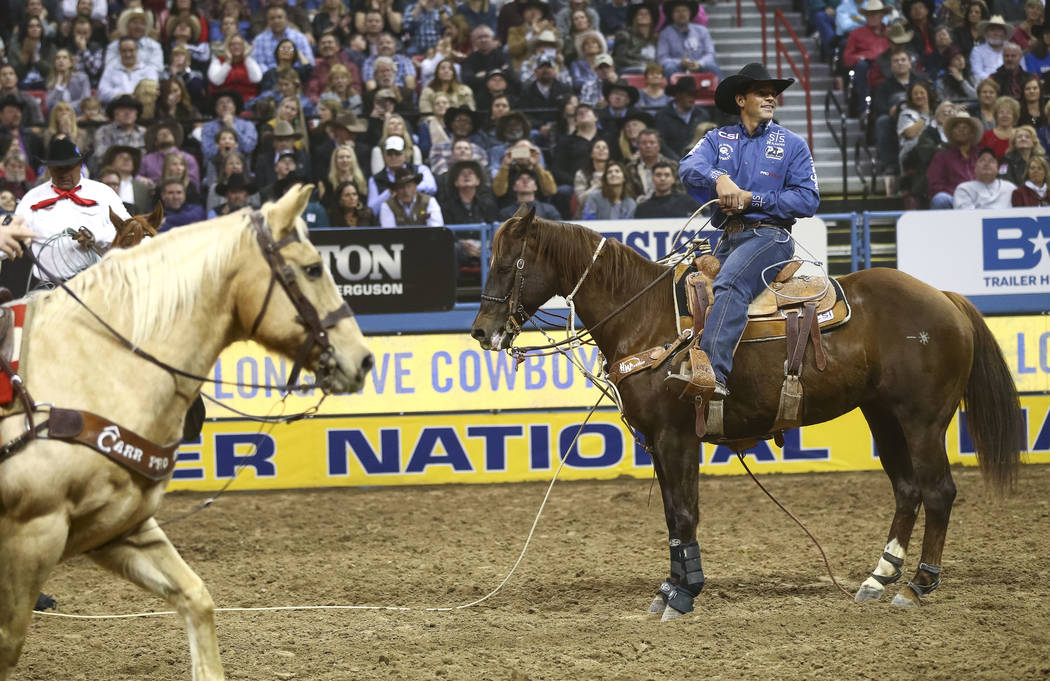Marcos Costa of Childress, Texas looks to the crowd after taking part in the tie-down roping competition in the tenth go-round of the National Finals Rodeo, Saturday, Dec. 16, 2017, at the Thomas  ...