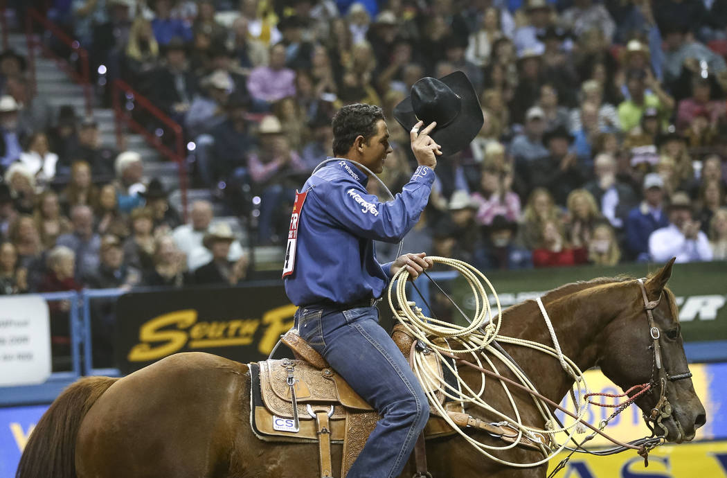 Marcos Costa of Childress, Texas waives to the crowd after taking part in the tie-down roping competition in the tenth go-round of the National Finals Rodeo, Saturday, Dec. 16, 2017, at the Thomas ...