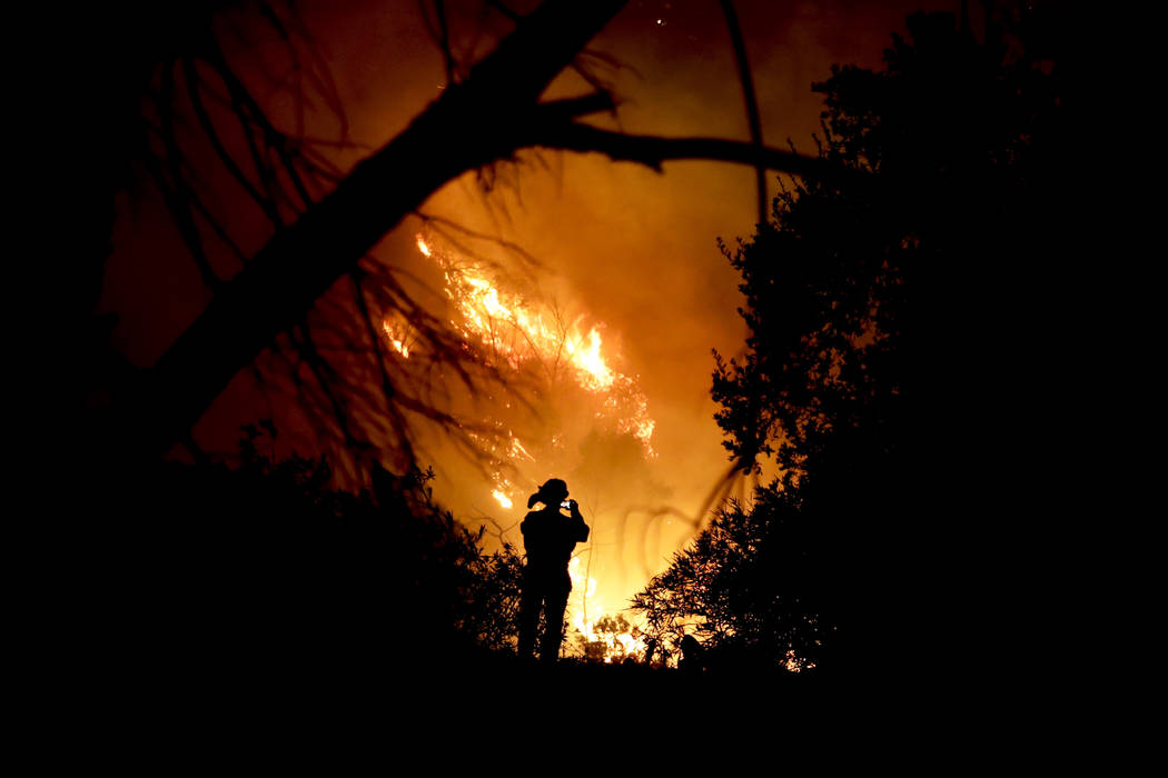 A firefighter takes a cell phone picture during a wildfire Saturday, Dec. 16, 2017, in Montecito, Calif. The so-called Thomas Fire is now the third-largest in California history. (Chris Carlson/AP)