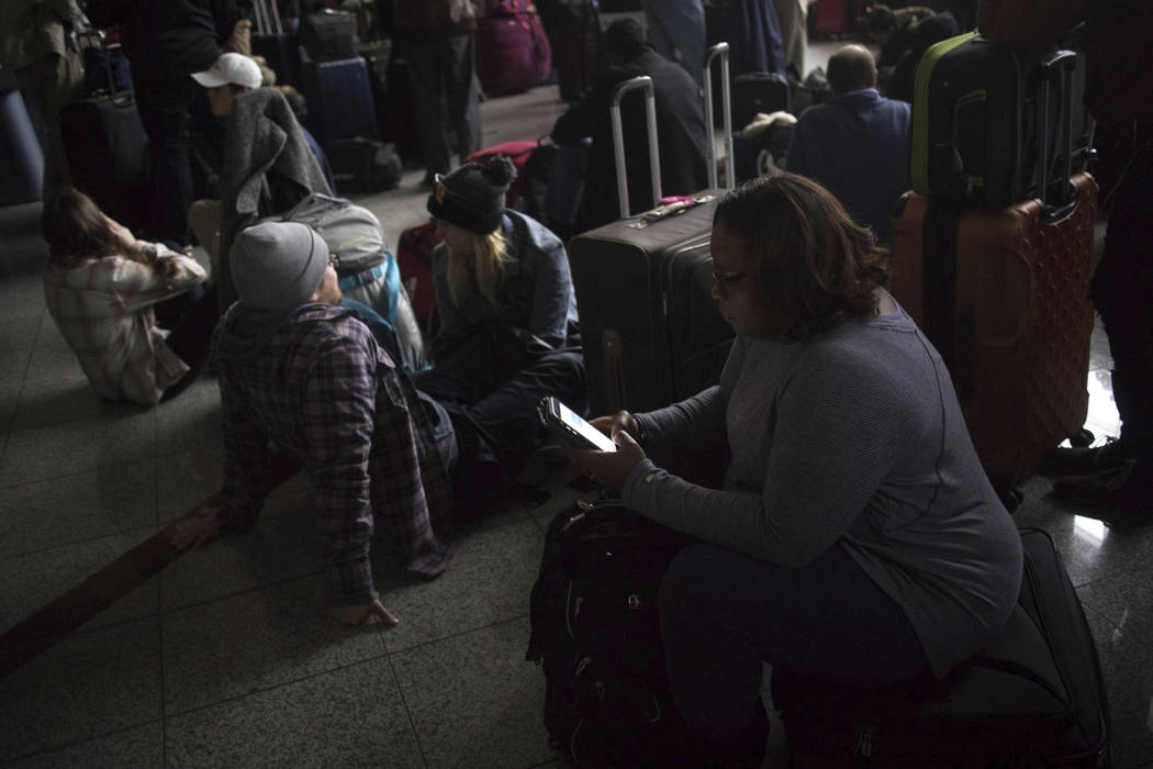 Passengers wait for the lights to come back on at Hartsfield-Jackson International Airport Sunday, Dec. 17, 2017. Authorities say a power outage at the Hartsfield-Jackson Atlanta International Air ...