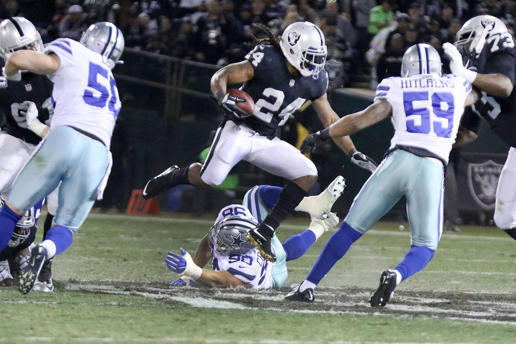 Oakland Raiders running back Marshawn Lynch (24) hurdles over Dallas Cowboys defensive end Tyrone Crawford (98) as he runs with the football during the first half of a NFL game in Oakland, Calif., ...