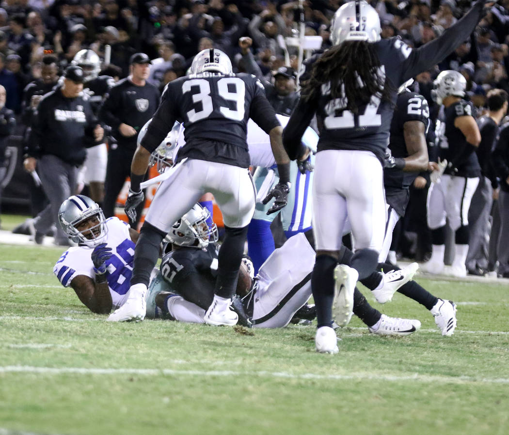 Oakland Raiders cornerback Sean Smith (21) intercepts a pass intended for Dallas Cowboys wide receiver Dez Bryant (88) as strong safety Keith McGill (39) and free safety Reggie Nelson (27) come in ...