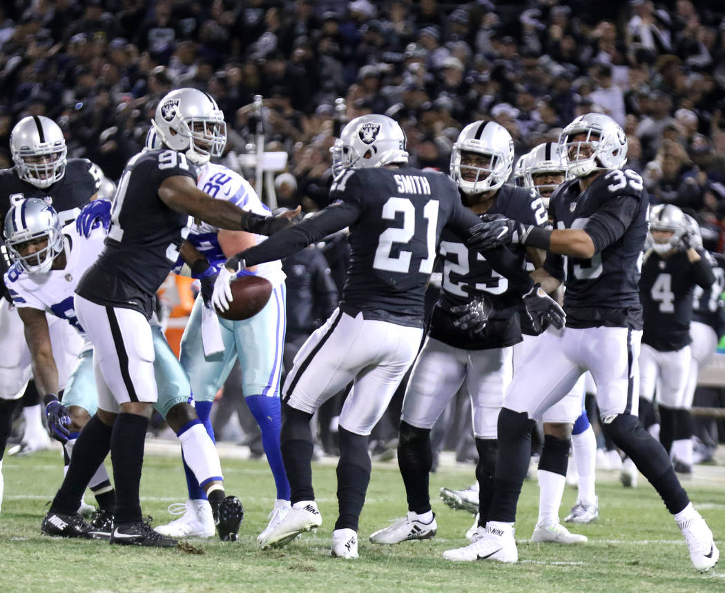 Oakland Raiders cornerback Sean Smith (21) celebrates his intercepted pass with linebacker Shilique Calhoun (91), cornerback Dexter McDonald (23) and strong safety Keith McGill (39) during the fir ...