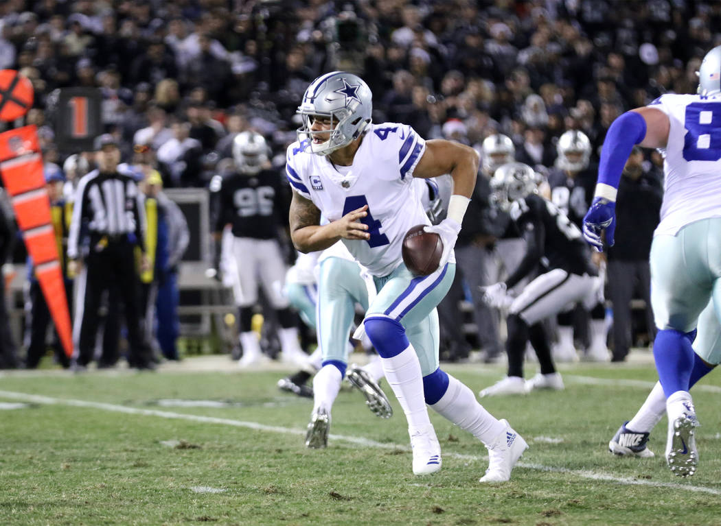 Dallas Cowboys quarterback Dak Prescott (4) scrambles with the football against the Oakland Raiders during the first half of a NFL game in Oakland, Calif., Sunday, Dec. 17, 2017. Heidi Fang Las Ve ...