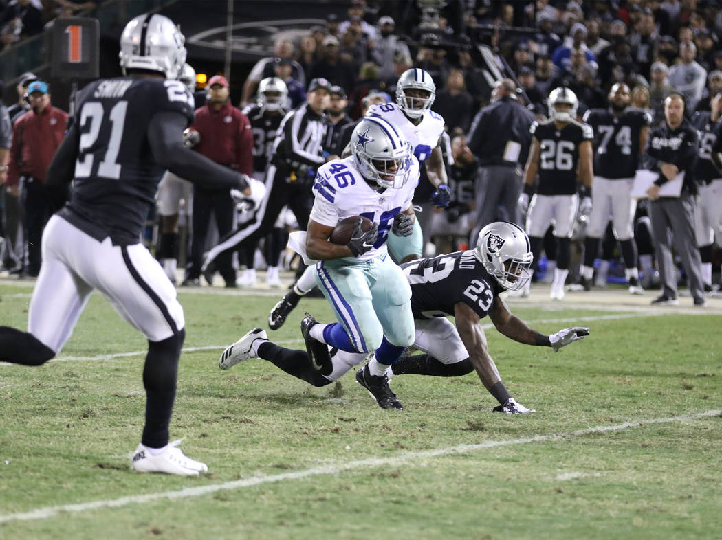Dallas Cowboys running back Alfred Morris (46) runs with the football as Oakland Raiders cornerback Dexter McDonald (23) misses a tackle during the first half of a NFL game in Oakland, Calif., Sun ...