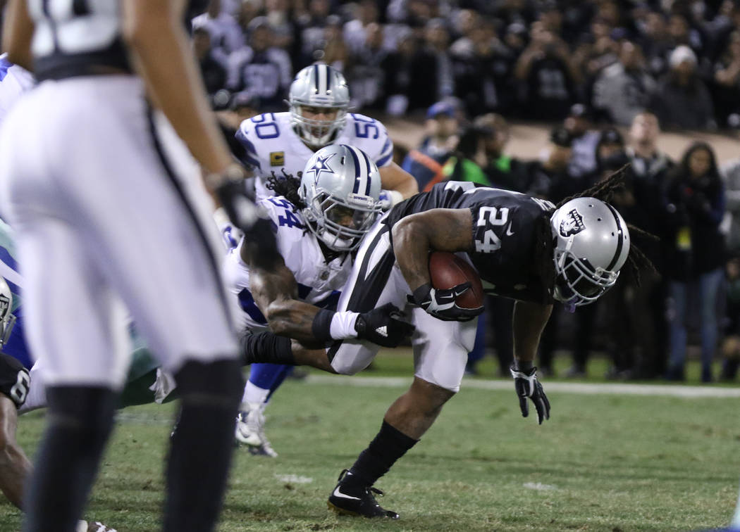 Oakland Raiders running back Marshawn Lynch (24) tries to break a tackle by Dallas Cowboys outside linebacker Jaylon Smith (54) during the first half of a NFL game in Oakland, Calif., Sunday, Dec. ...