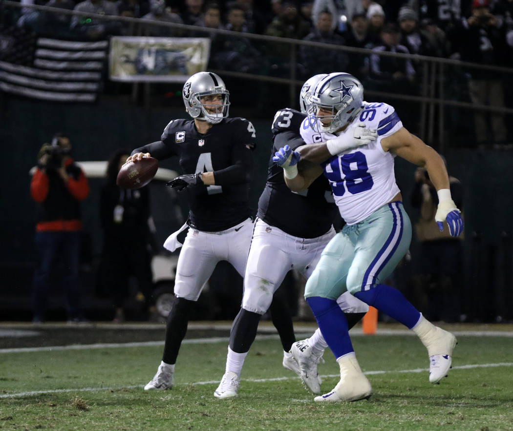 Oakland Raiders quarterback Derek Carr (4) drops back to pass as offensive tackle Marshall Newhouse (73) battles with Dallas Cowboys defensive end Tyrone Crawford (98) during the first half of a N ...