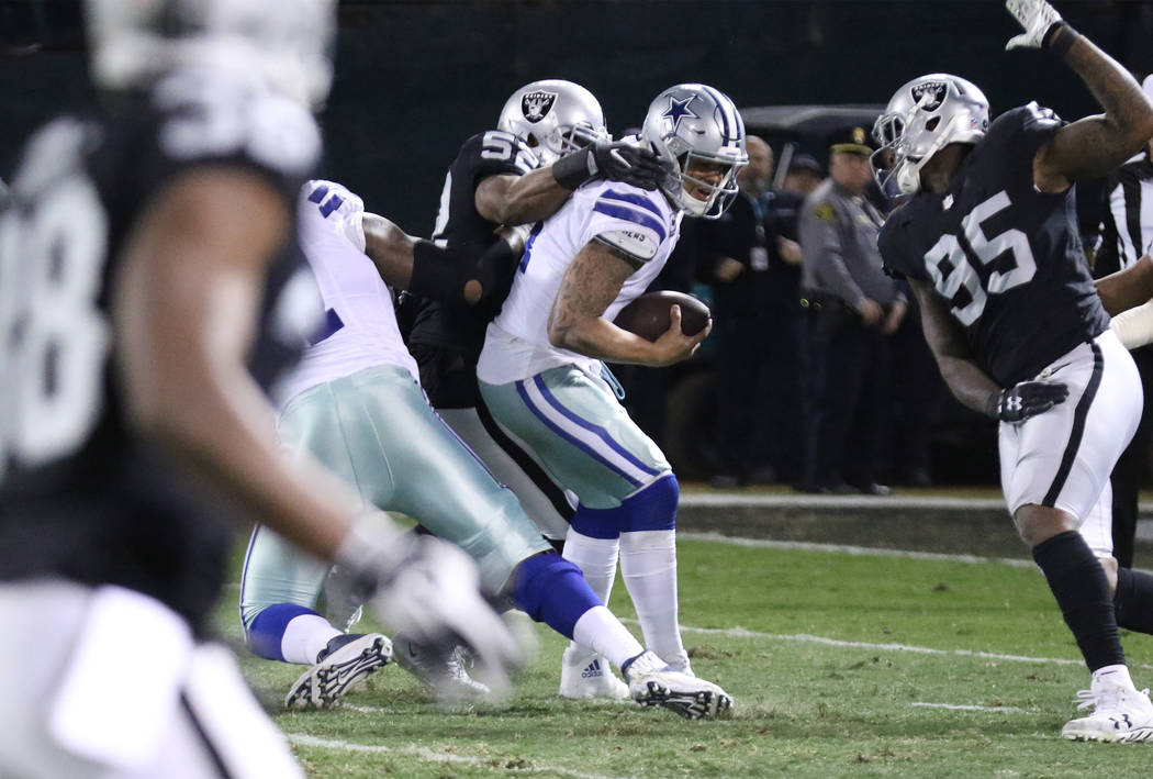 Oakland Raiders defensive end Khalil Mack (52) sacks Dallas Cowboys quarterback Dak Prescott (4) during the first half of a NFL game in Oakland, Calif., Sunday, Dec. 17, 2017. Heidi Fang Las Vegas ...